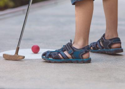 Happy little boy  playing mini golf.